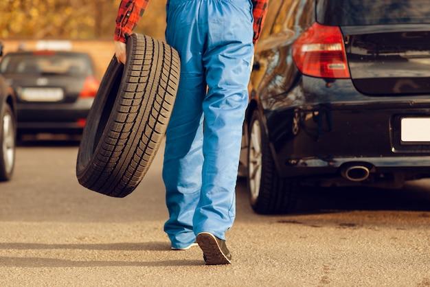 Travailleur masculin en uniforme détient pneu