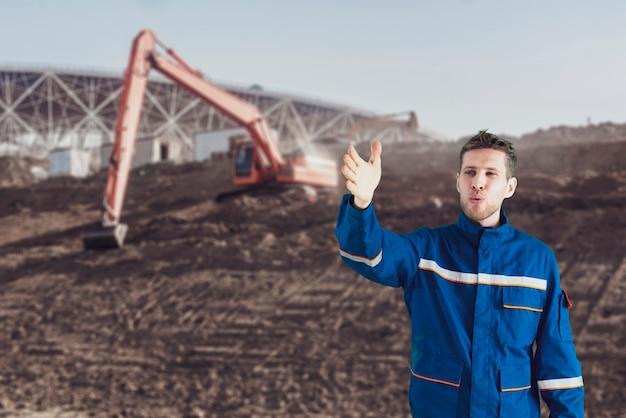Un travailleur masculin en uniforme effectuant des travaux au bord de la route en construisant une nouvelle autoroute