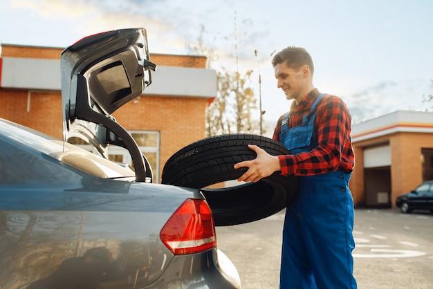 Travailleur masculin en uniforme met le pneu dans le coffre