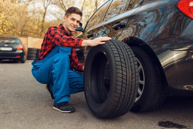 Travailleur masculin en uniforme résoudre le problème avec le pneu