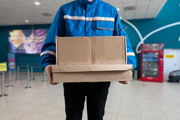 Un travailleur masculin en uniforme tenant une boîte, processus de livraison d'expédition, distribution des affaires