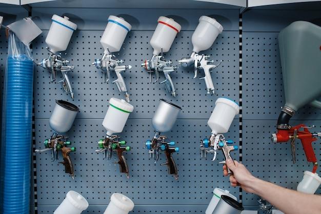 Un travailleur masculin en uniforme tient un pistolet pneumatique à peinture dans un magasin d'outils