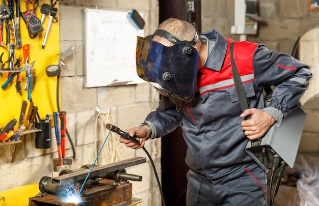 Travailleur en masque de protection avec une machine à souder portable
