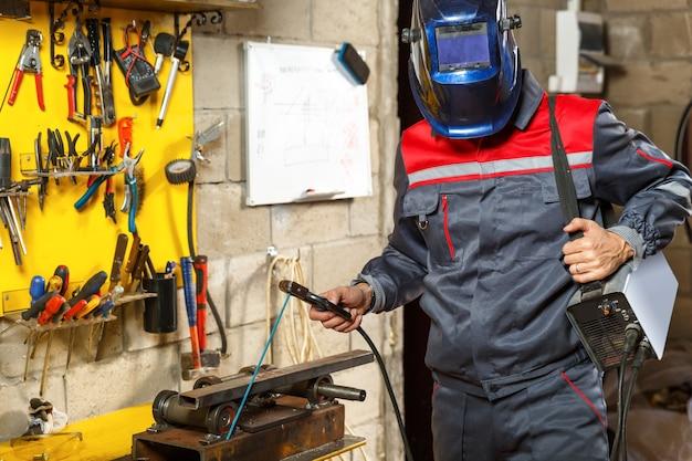 Travailleur avec masque de protection en métal de soudage à la maison de construction