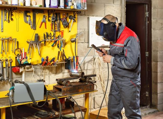 Travailleur avec masque de protection en métal de soudage