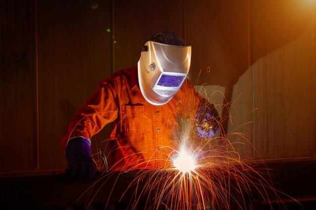 Travailleur avec masque de protection soudant le métal dans un entrepôt industriel.
