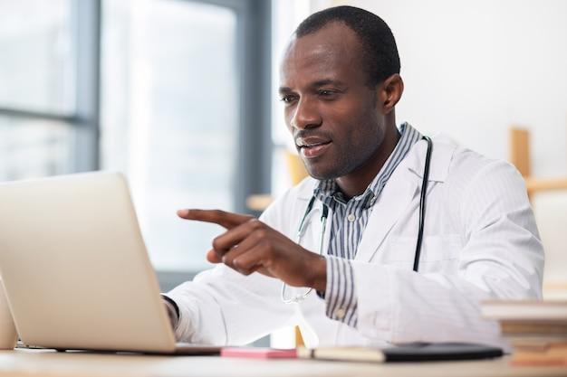 Travailleur médical concentré lisant un article scientifique tout en ayant une pause