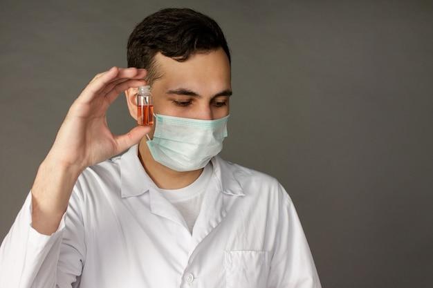 Un travailleur médical détient un vaccin et porte un masque pour se protéger du coronavirus