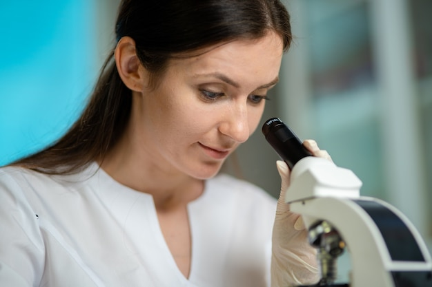 Travailleur médical féminin effectuant des recherches en laboratoire avec un microscope, des tubes à essai, des médicaments, des produits chimiques et des analyses examinant les virus et autres maladies humaines