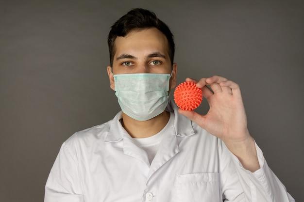 Un travailleur médical porte un masque et détient un modèle du coronavirus.