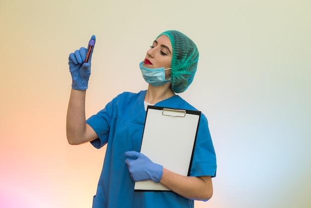 Travailleur médical avec des tubes à essai avec du sang posent en laboratoire