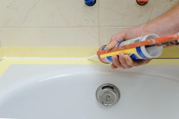 Le travailleur met du mastic silicone pour calfeutrer le joint entre la baignoire et le mur.