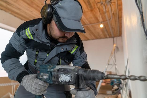 Le travailleur met des écouteurs spéciaux pour l'isolation acoustique et perce un trou dans le mur avec un poinçon