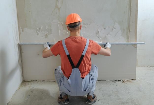 Le travailleur met un plâtre de gypse.