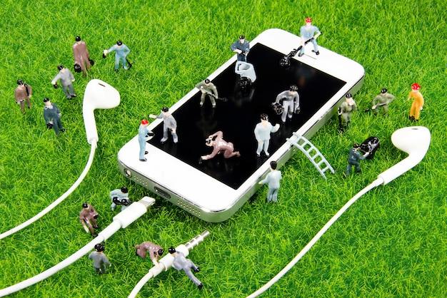 Travailleur de mini jouet travaillant sur un smartphone sur l'herbe