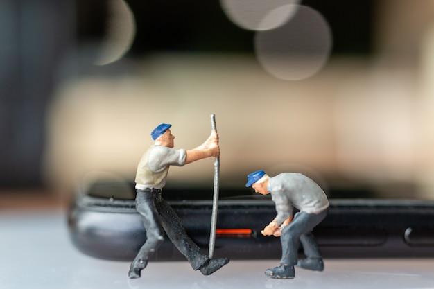 Travailleur miniature de personnes avec des outils réparant le téléphone portable, concept de dispositifs électroniques