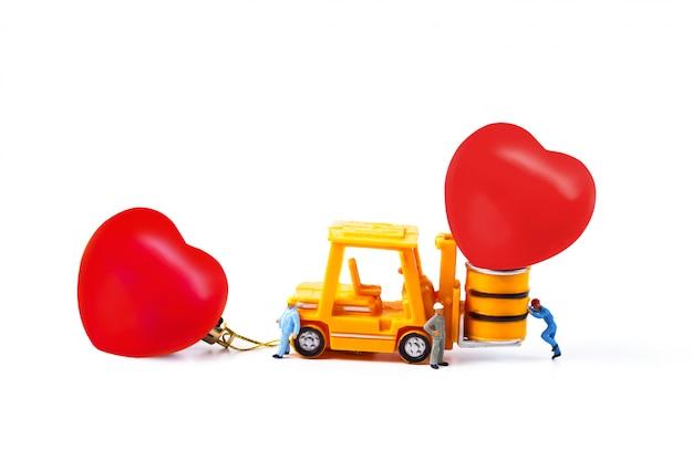 Travailleur miniature et petit chariot élévateur avec boule coeur, saint valentin.