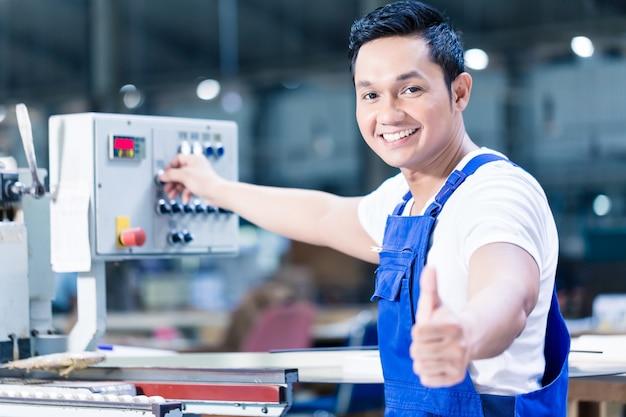 Travailleur montrant les pouces vers le haut dans l'usine de production asiatique debout devant un tableau de commande de la machine