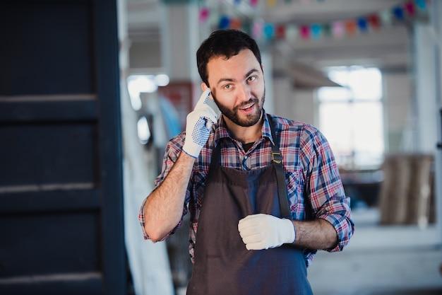 Travailleur montre son doigt dans un gant en tissu expliquant quelque chose à quelqu'un