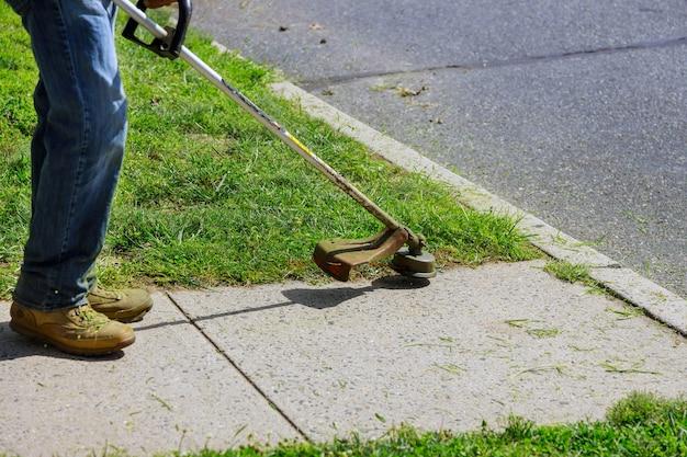 Un travailleur municipal dans une tondeuse à gazon tond de l'herbe verte et fraîche sur la pelouse près d'un immeuble résidentiel.