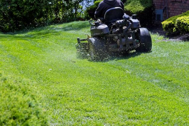 Travailleur municipal tond la tondeuse à gazon jardinier coupe l'herbe