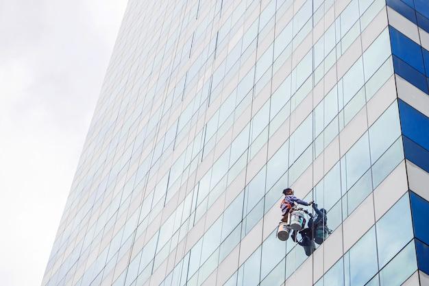 Le travailleur nettoie la fenêtre en verre de l'immeuble de grande hauteur avec le grimpeur suspendu.