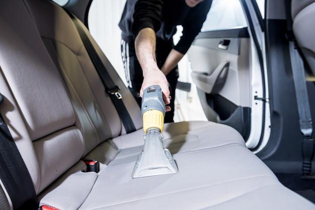 Travailleur nettoie l'intérieur de la voiture avec un aspirateur