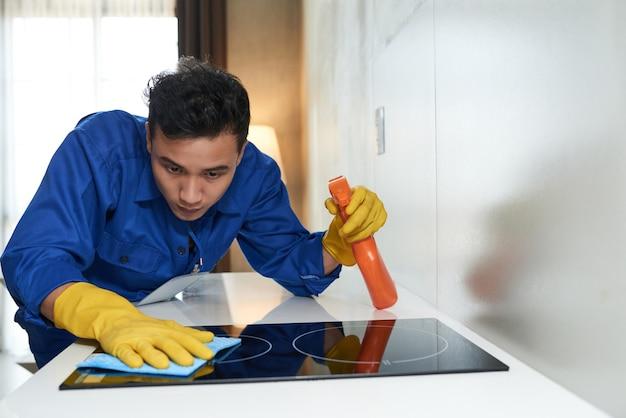 Travailleur nettoyant la surface du poêle