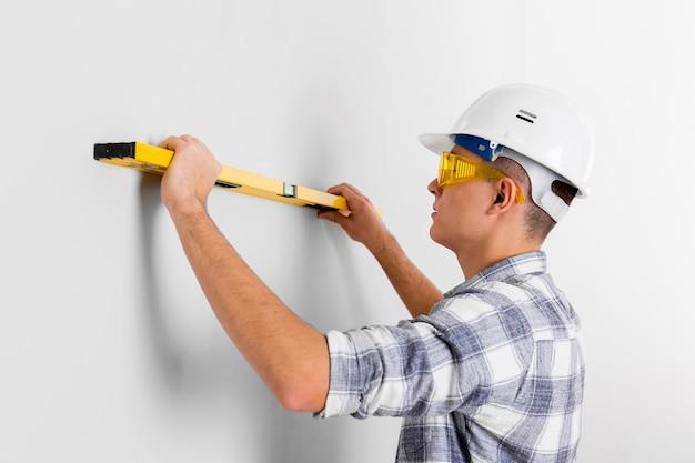 Travailleur avec niveau à bulle sur un mur