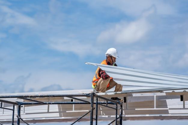 Travailleur avec des outils de couvreur portant un équipement de protection installant un nouveau toit sur le toit supérieur du chantier de construction, toit en métal.
