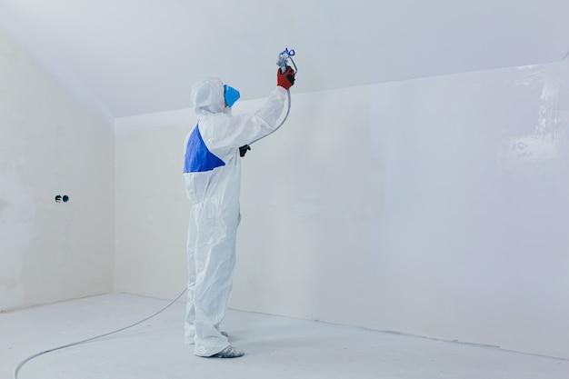Travailleur peint le mur avec un pulvérisateur dans une maison nouvellement construite