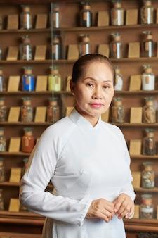 Travailleur de la pharmacie féminine debout sur des étagères