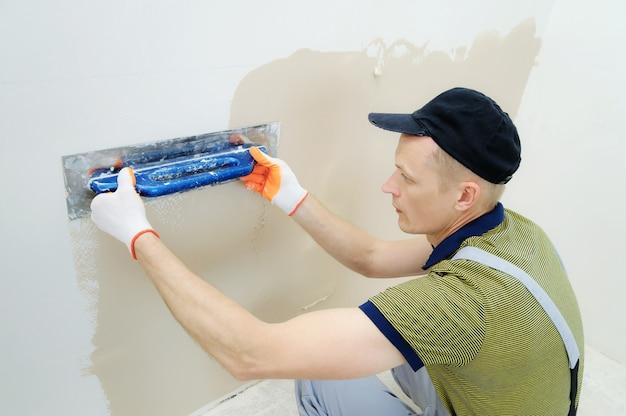 Travailleur plâtrant un mur dans un appartement de bas en haut