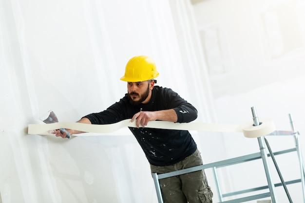 Travailleur plâtrant mur en plaques de plâtre.