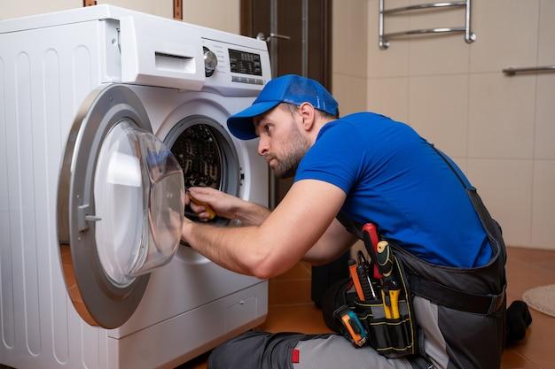 Travailleur plombier homme répare une machine à laver dans l'installation de machine à laver à domicile ou réparer l'appareil de connexion plombier