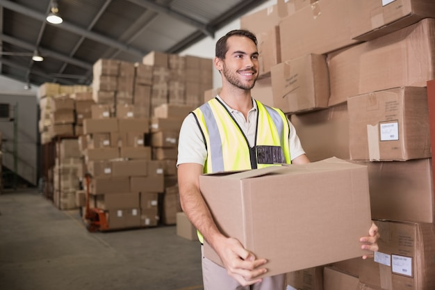 Travailleur portant la boîte dans l'entrepôt