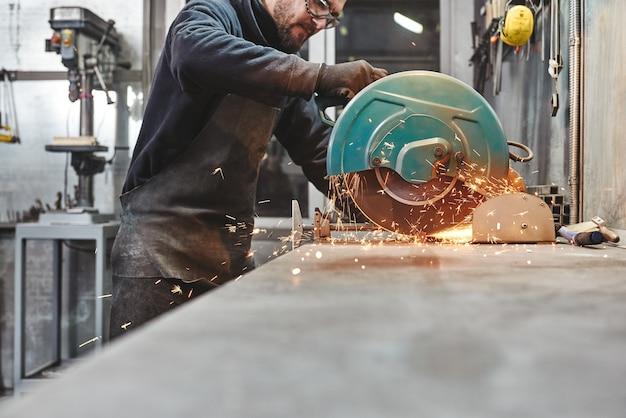 Travailleur portant des gants et des lunettes de protection spéciaux utilisant un broyeur pour polir un morceau de métal