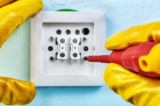 Un travailleur portant des gants de protection jaunes serre la vis dans un interrupteur d'éclairage standard européen avec un tournevis diélectrique.