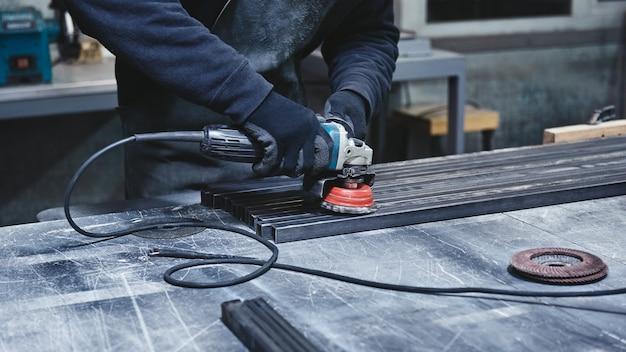 Travailleur portant des gants de protection spéciaux utilisant un broyeur pour polir un morceau de cadre métallique