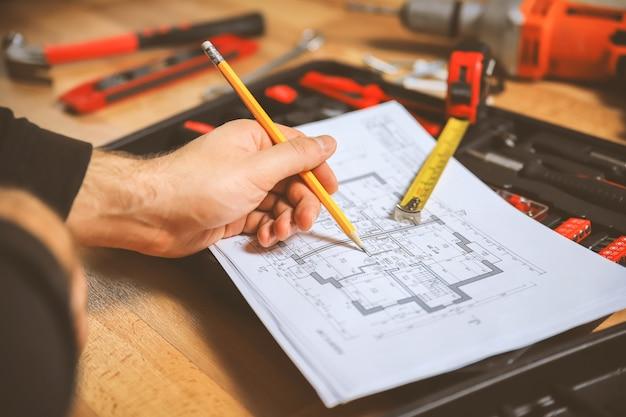 Travailleur prendre des notes dans le plan technique de l'appartement