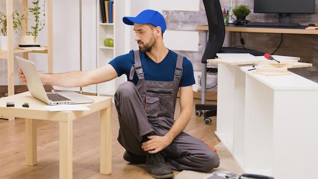 Un travailleur professionnel assemble une étagère et consulte des instructions sur un ordinateur portable. bricoleur aidant les personnes qui emménagent dans une nouvelle maison.