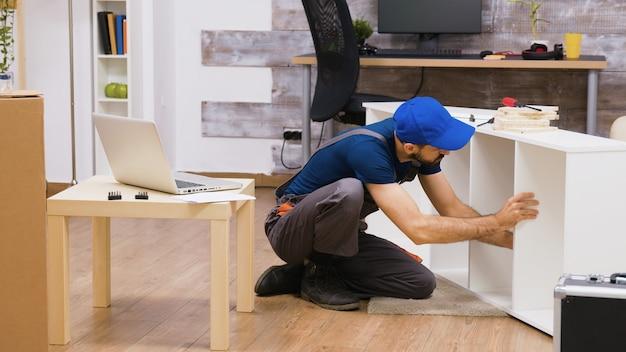 Un travailleur professionnel en salopette consulte les instructions d'assemblage de meubles à partir d'un ordinateur portable. ouvrier coiffé d'une casquette.