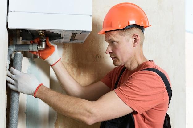 Le travailleur raccorde les tuyaux à une chaudière à gaz domestique.