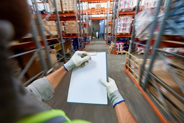 Travailleur remplissant des documents dans l'entrepôt