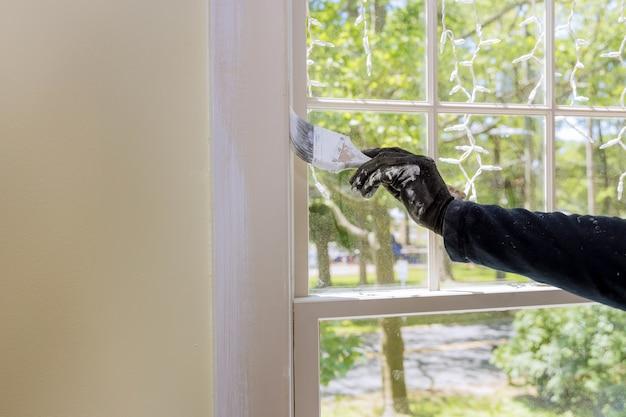 Travailleur de la restauration à domicile peignant à l'aide d'un pinceau sur une couche de couleur blanche une garniture de cadre de fenêtre