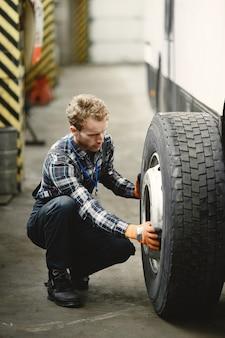 Travailleur avec une roue. remplacement de la roue. homme en uniforme