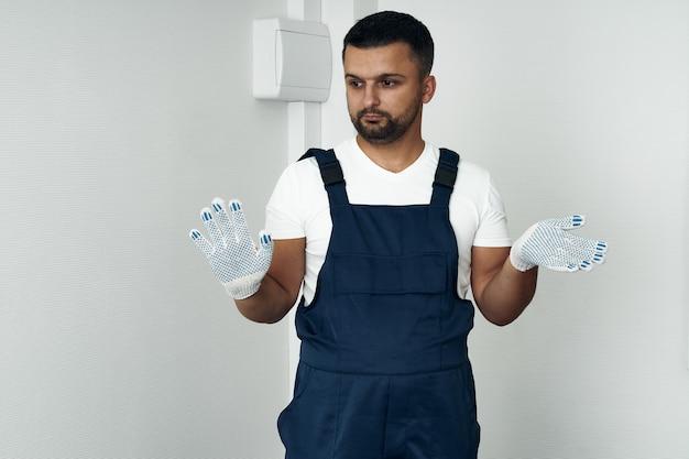 Travailleur en salopette et chaussures blanches