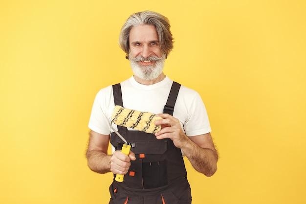 Travailleur en salopette. homme avec des outils. senior avec rouleau à peinture.