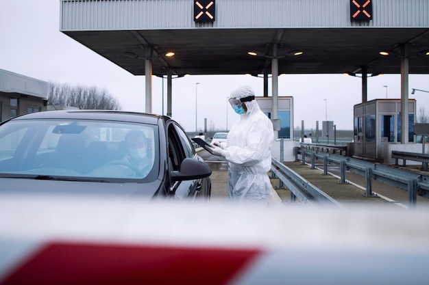 Travailleur de la santé médicale en combinaison blanche de protection contrôlant les passagers et test pcr au passage de la frontière en raison de la pandémie mondiale du virus corona