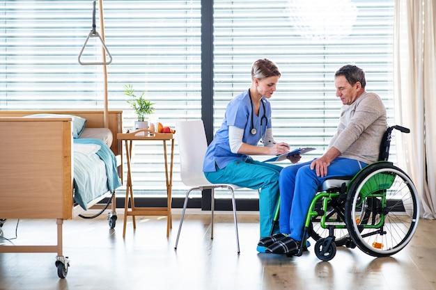 Un travailleur de la santé et un patient âgé en fauteuil roulant à l'hôpital ou à la maison, en train de parler.